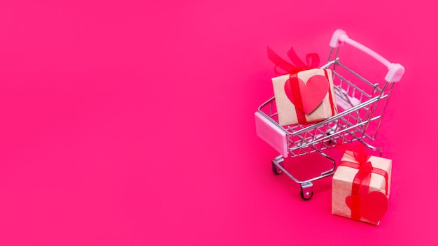 Piccolo carrello della spesa con scatole regalo su sfondo rosso-rosa. fai regali con amore a san valentino Foto Premium