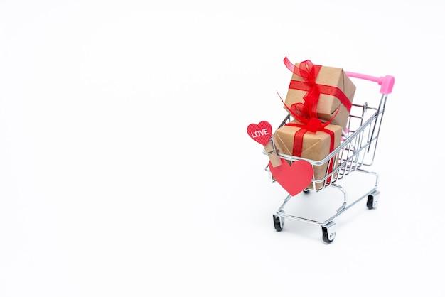 Piccolo carrello della spesa con scatole regalo su sfondo bianco Foto Premium