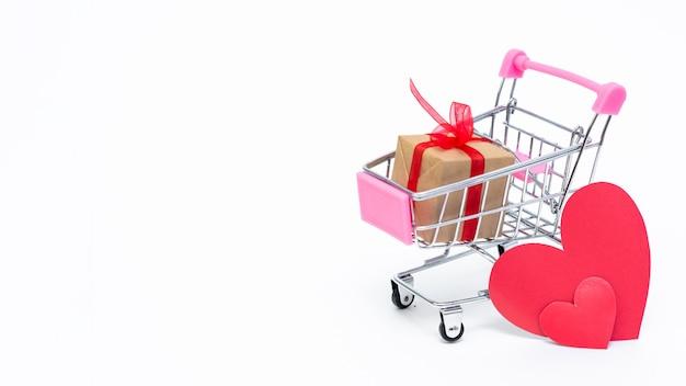Piccolo carrello della spesa con scatole regalo sulla superficie bianca. fai regali con amore a san valentino Foto Premium