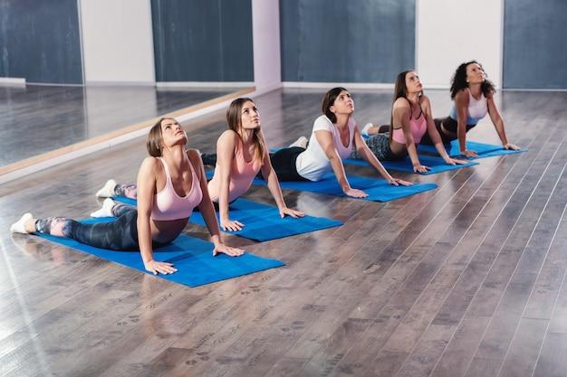 Il piccolo gruppo di donne che fanno l'yoga della cobra posa sulla stuoia. Foto Premium