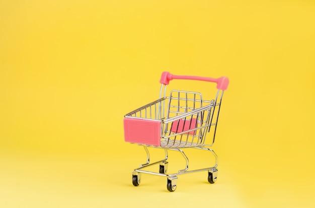 Piccolo supermercato drogheria spingere il carrello giocattolo per lo shopping con ruote su sfondo colorato giallo. Foto Premium