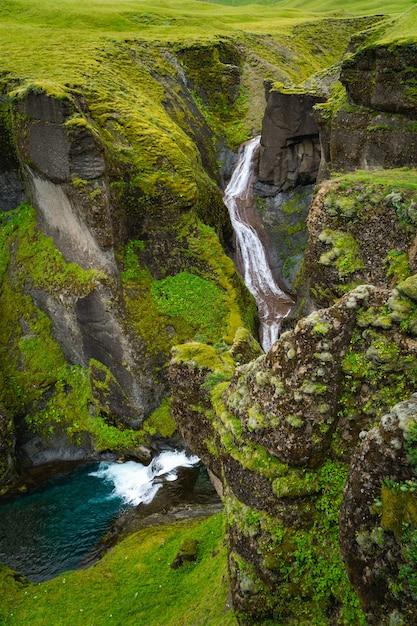 Piccola cascata che alimenta in un canyon muscoso in islanda Foto Premium