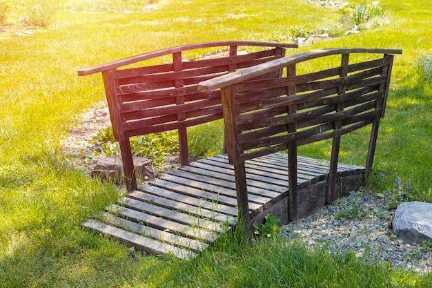 Piccolo ponte di legno in un bellissimo giardino verde. Foto Premium