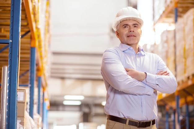 Responsabile della logistica intelligente che indossa un casco mentre è al lavoro nel magazzino Foto Premium