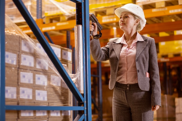 Bella donna intelligente che usa uno scanner mentre fa il controllo dell'inventario Foto Premium