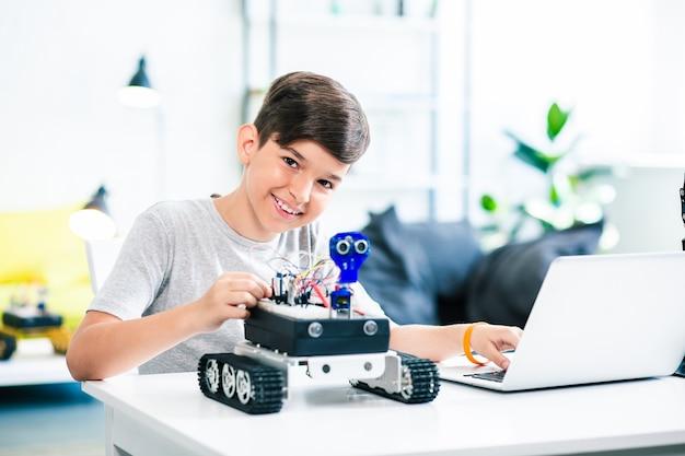 Ragazzo positivo intelligente che prova il robot mentre si prepara per le lezioni di ingegneria a casa Foto Premium