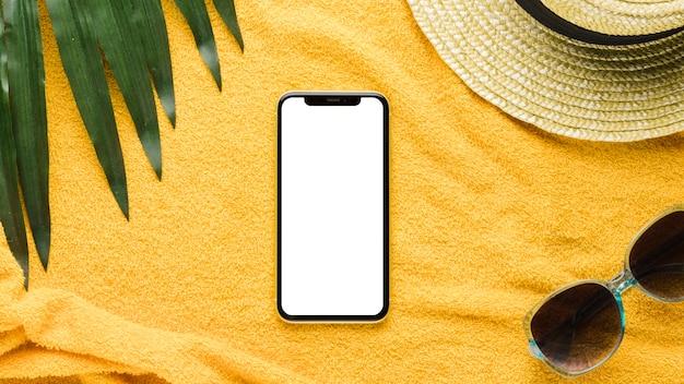 Accessori smartphone e spiaggia su sfondo chiaro Foto Premium