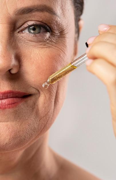Donna anziana sorridente che usa il siero per le rughe della bocca Foto Premium