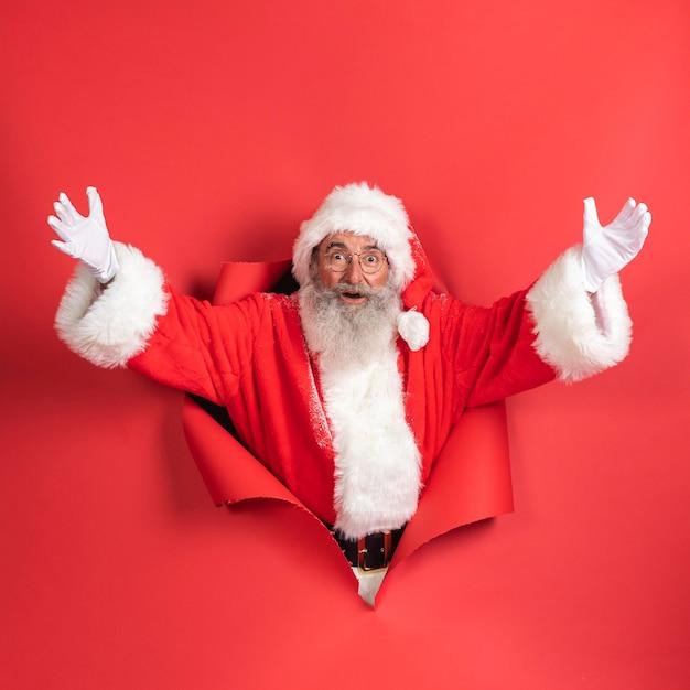 Uomo sorridente in costume da babbo natale che esce di carta Foto Premium