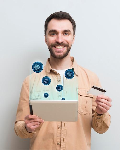 Uomo di smiley che compera online sul suo tablet Foto Premium