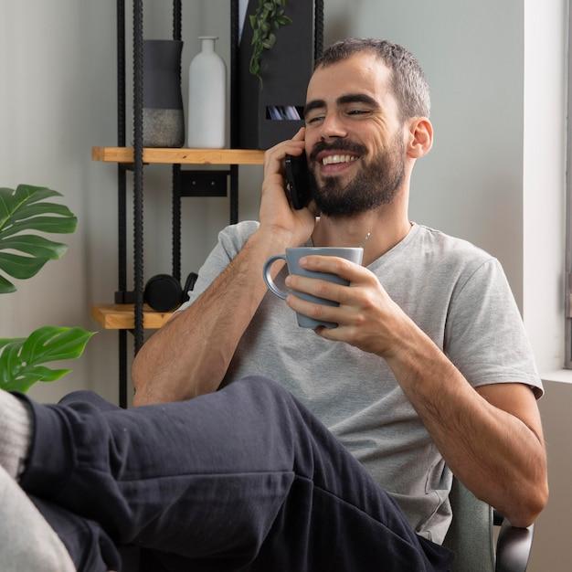 Uomo di smiley che parla al telefono mentre beve il caffè a casa Foto Premium