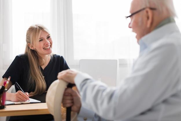 Uomo maggiore di smiley in una casa di cura con infermiera femminile Foto Premium