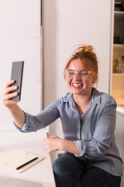 Insegnante di smiley utilizza lo smartphone per tenere una lezione online Foto Premium