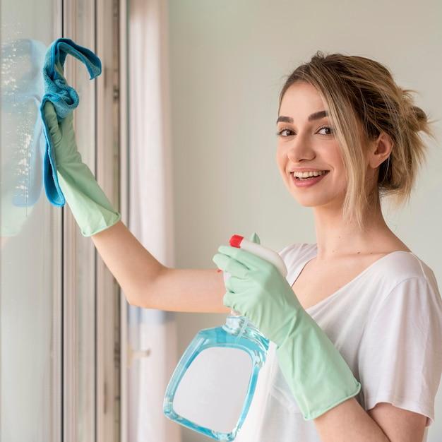 Finestra di pulizia della donna di smiley con il panno e la soluzione di pulizia Foto Premium