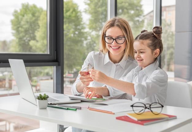 Donna di smiley che aiuta sua figlia a fare i compiti Foto Premium