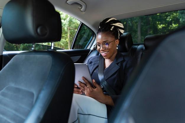 Donna sorridente guardando tablet mentre era seduto sul sedile posteriore della sua auto Foto Premium