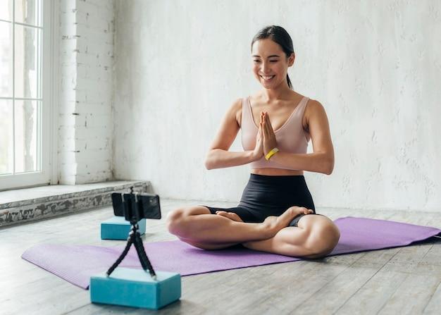 Donna di smiley meditando sul tappetino fitness Foto Premium