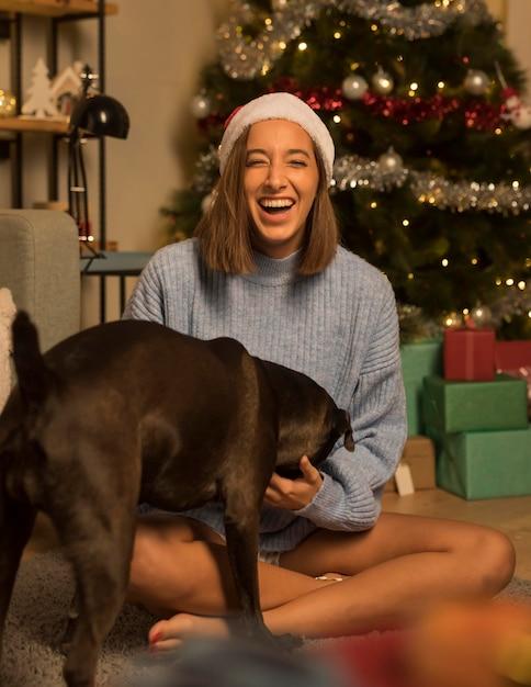 Donna di smiley con il cane in posa mentre indossa il cappello della santa Foto Premium