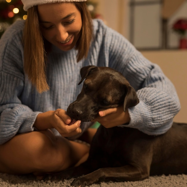 Donna sorridente con il suo cane a natale Foto Premium