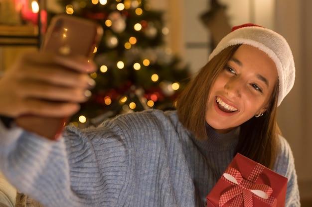 Donna di smiley con il cappello della santa che prende selfie mentre tiene il regalo di natale Foto Premium
