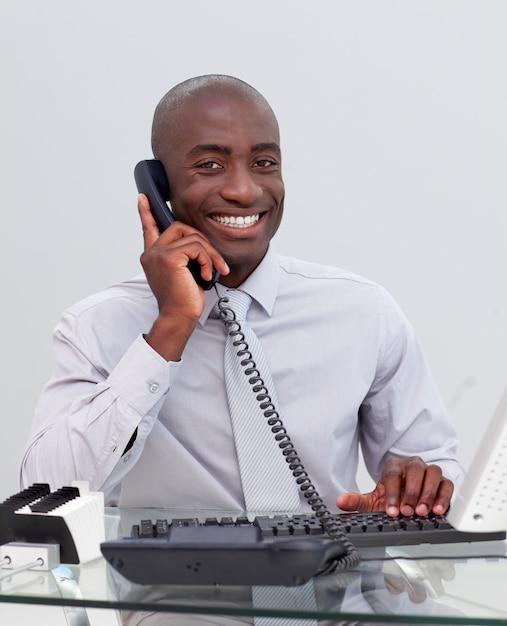 Uomo d'affari afroamericano sorridente sul telefono nell'ufficio Foto Premium