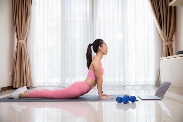 Sorridente donna asiatica in cobra posa praticare yoga e guardare video sul laptop, formazione in salotto Foto Premium