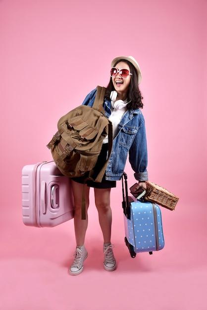 Il viaggiatore asiatico sorridente della donna porta il sacco di bagaglio Foto Premium