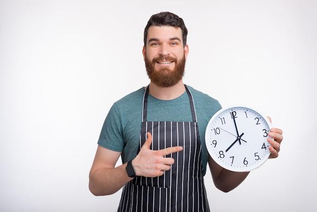 Il grembiule d'uso sorridente dell'uomo barbuto sta tenendo un orologio bianco mentre sorrideva sulla parete bianca Foto Premium