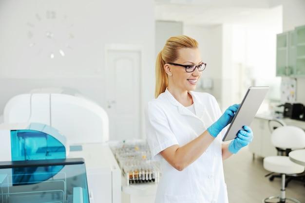 Assistente di laboratorio bionda sorridente con guanti di gomma che tengono compressa e immissione dei risultati del test. Foto Premium