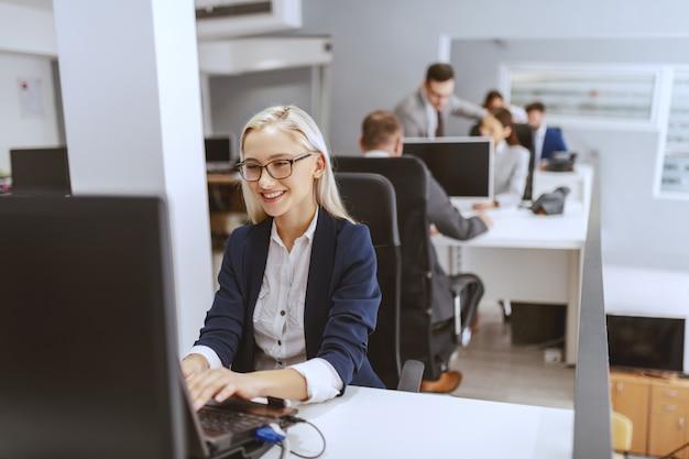 Sorridente bionda imprenditrice caucasica seduto al suo posto di lavoro e utilizzando il computer. mani sulla tastiera. Foto Premium