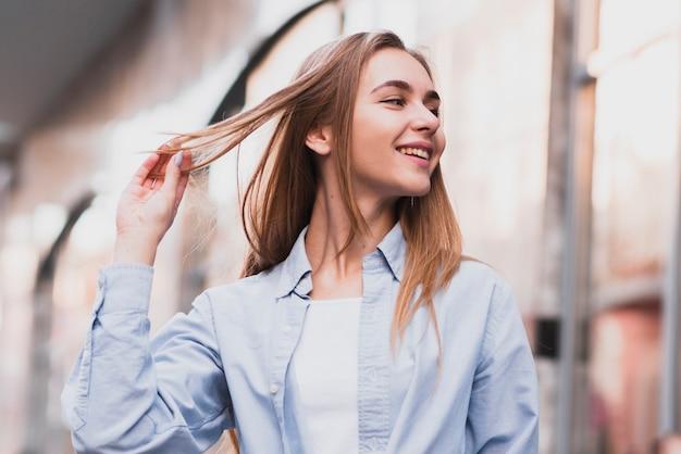 Ragazza bionda sorridente che organizza i suoi capelli Foto Premium
