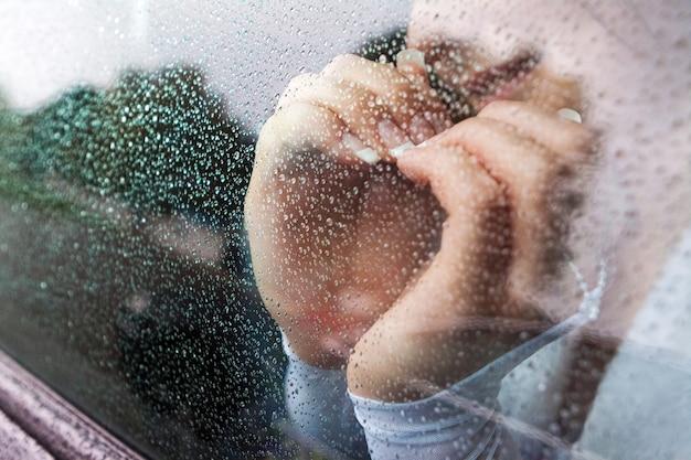 La sposa sorridente ha incrociato le mani a forma di cuore, la vista attraverso il vetro del finestrino dell'auto durante la pioggia Foto Premium