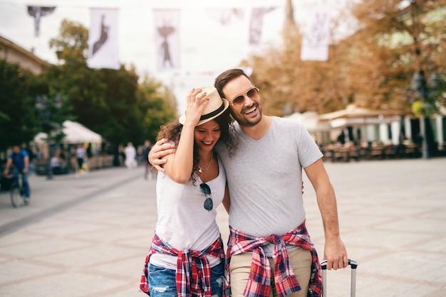 Coppie caucasiche sorridenti che camminano sul viale e sull'abbracciare. cappello della tenuta della donna mentre bagagli della tenuta dell'uomo. concetto di viaggio. Foto Premium