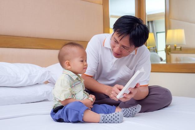 Padre sorridente e suo figlio leggendo la storia della buonanotte Foto Premium
