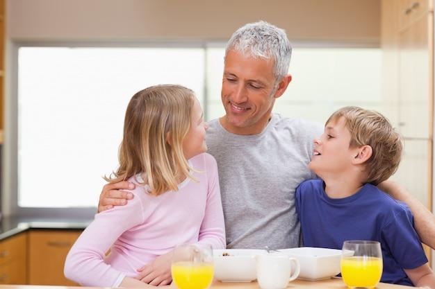 Padre sorridente con i suoi figli al mattino Foto Premium
