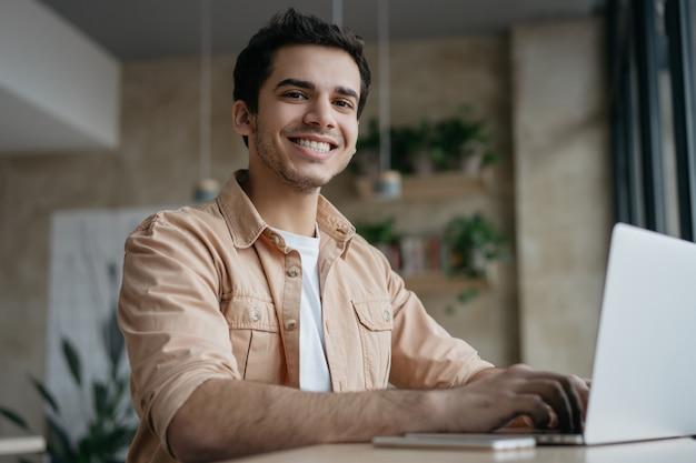 Copywriter sorridente delle free lance facendo uso del computer portatile, funzionante dalla casa Foto Premium
