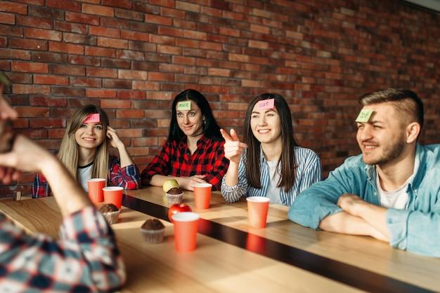 Amici sorridenti che giocano le note dell'autoadesivo al gioco della fronte. Foto Premium