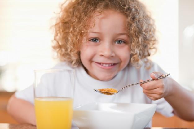 Ragazza sorridente facendo colazione in cucina Foto Premium