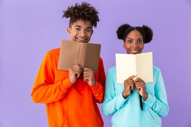 Ragazzo e ragazza sorridente che tiene e che legge libri, isolato sopra la parete viola Foto Premium