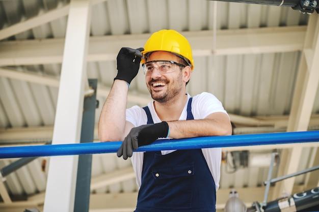 Lavoratore caucasico bello sorridente nel complesso e con il casco sulla testa che si appoggia l'inferriata. produzione di olio. Foto Premium