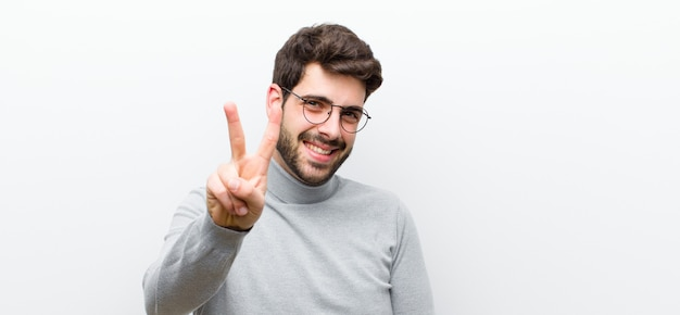 Sorridente e amichevole, mostrando il numero due o il secondo con la mano in avanti, il conto alla rovescia Foto Premium