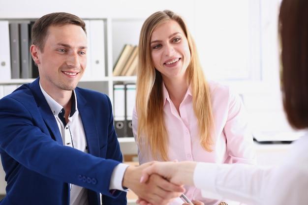 L'uomo e la donna sorridenti si stringono la mano come ciao in ufficio Foto Premium