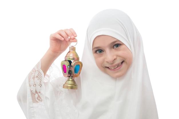 Sorridente ragazzina musulmana in hijab che tiene la lanterna del ramadan Foto Premium