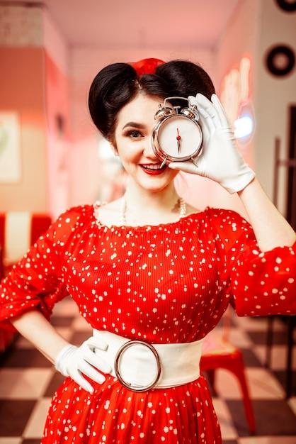 Sorridente ragazza pin up in posa con sveglia, interni caffè vintage, popolare moda americana anni '50 e '60. abito rosso con pois, trucco luminoso Foto Premium