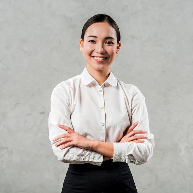 Il ritratto sorridente di una giovane donna asiatica con le sue armi ha attraversato lo sguardo alla macchina fotografica contro il muro di cemento grigio Foto Premium