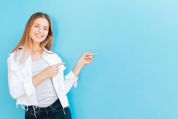 Ritratto sorridente di una giovane donna che indica la sua barretta contro la priorità bassa blu Foto Premium
