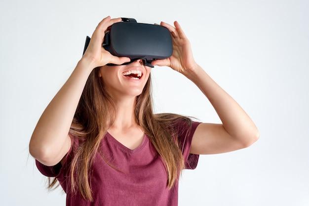 Cuffia avricolare d'uso sorridente degli occhiali di protezione di realtà virtuale della donna positiva, scatola del vr. connessione, tecnologia, nuova generazione, concetto di progresso. ragazza che prova a toccare gli oggetti nella realtà virtuale. studio girato su grigio Foto Premium