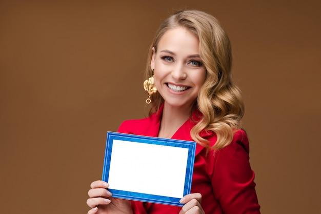 Signora graziosa sorridente con la posa della carta in bianco Foto Premium
