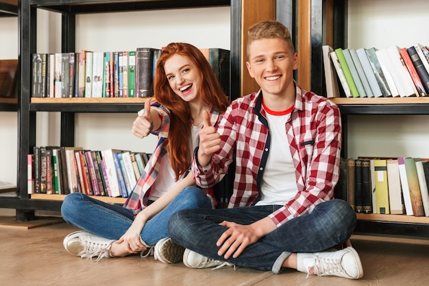 Sorridente coppia adolescente seduto su un pavimento presso lo scaffale per libri Foto Premium