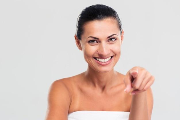 Donna sorridente in asciugamano puntare il dito alla telecamera Foto Premium